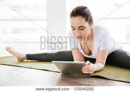 Pretty young woman doing twine and using tablet in yoga studio