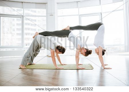 Group of two young women and man practicing acro yoga in studio together