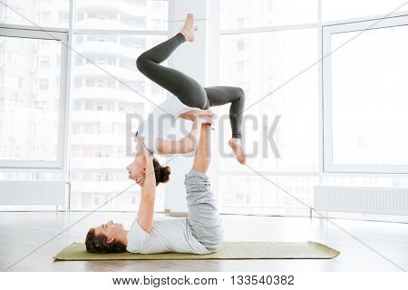 Pacified couple doing acro yoga in studio together