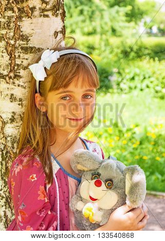 Portrait of little cute smiling girl with a toy in her hands