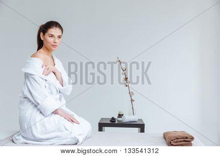 Portrait of attractive gentle young woman in bathrobe in spa salon
