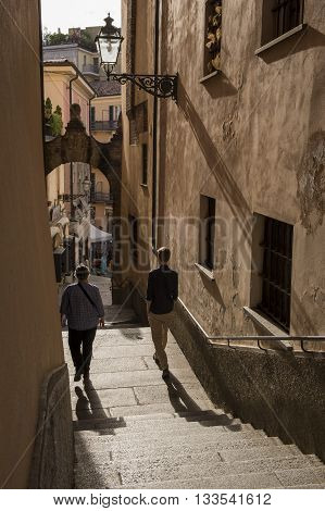 Acqui Terme Italy - May 29 2016: Small street with stairs and tourists in Acqui Terme Piedmont Italy.