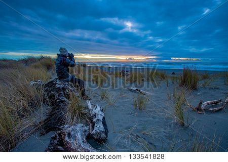 tourist man taking a photography at hokitika beach south island new zealand important traveling destination in west coast