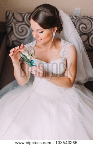 Close up portrait of beautiful caucasian mid adult bride holding cute little boutonniere.