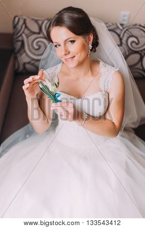 Close up portrait of beautiful caucasian mid adult bride sitting and holding cute little boutonniere.