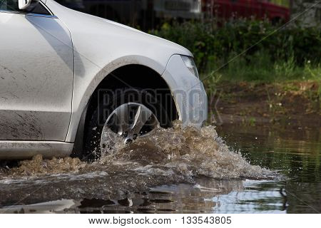 cars driving on a flooded road during a flood caused by heavy rain,