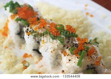 Sushi roll with fish roe and sesame seeds and spring onion