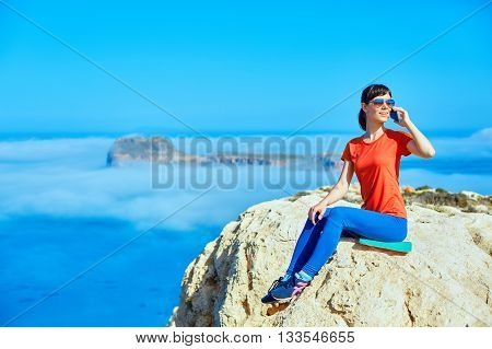 female traveler with backpack and phone sitting on the cliff against sea and blue sky at early morning. Balos beach on background, Crete, Greece. Woman talking by phone.