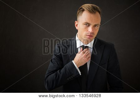 Business man fixing his tie and looking at the camera