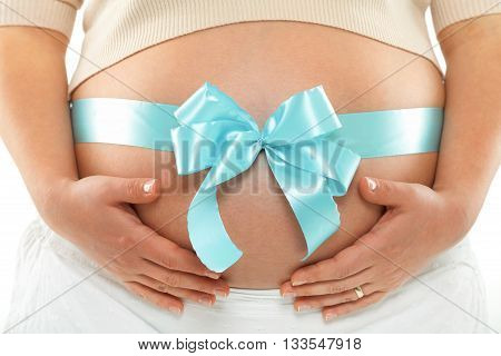 Pregnant woman with blue ribbon over her belly. Hands on tummy. Frontal view