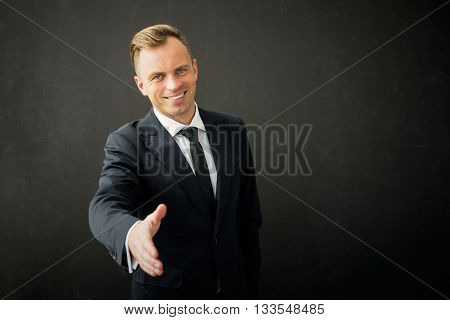 Happy business man with extended hand greeting