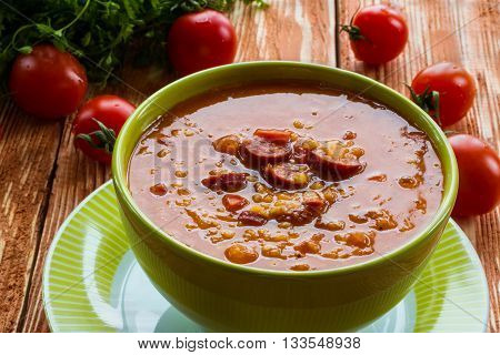 Soup: tomato soup with smoked sausage, tomatoes and lentil. Green bowl on wooden table. Small cherry tomatoes and green lettuce on table.