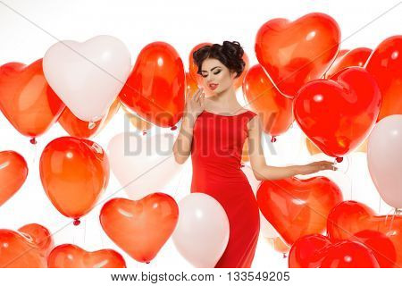 Beautiful girl, stylish fashion model with balloons in the shape of a heart. Woman on Valentine's Day. Symbol of love.