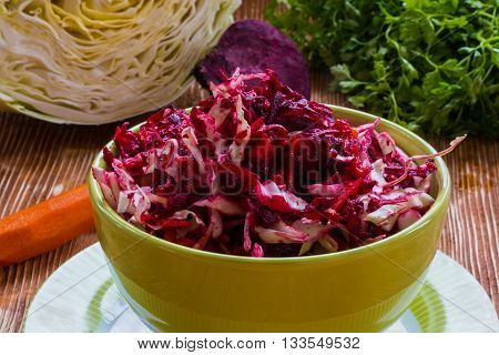Diet salad with beetroot, carrot, cabbage, olive oil and lemon. Served in a bowl on wooden background.