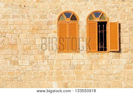 Two shuttered windows in stone wall of Jaffa mosque. Israel.