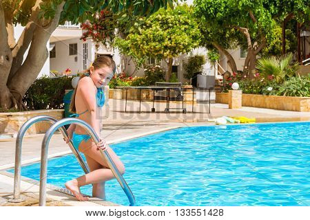 Cute little teenage girl in swimsuit standing at entrance to pool in middle of day. Relax and sunbathe by pool with clear blue water. Bali Rethymno Crete Greece