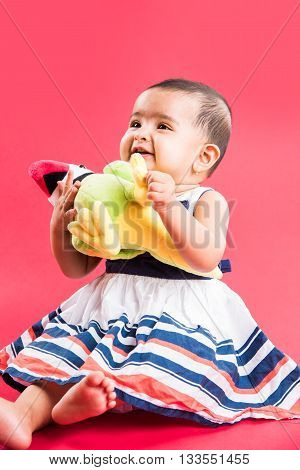Indian toddler playing over red background, cute little indian baby girl playing with toys, indian baby girl playing, asian infant playing