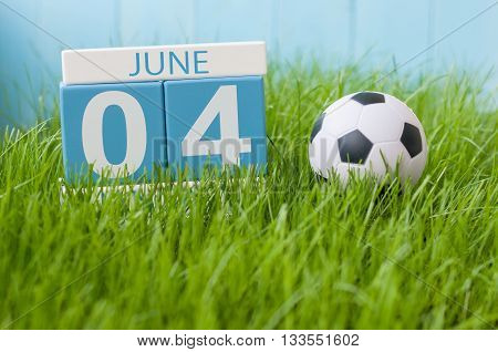 June 4th. Image of june 4 wooden color calendar on green grass background with football outfit. Summer day.