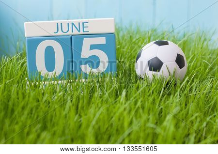 June 5th. Image of june 5 wooden color calendar on green grass background with football outfit. Summer day.