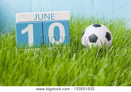 June 10th. Image of june 10 wooden color calendar on green grass background with football outfit. Summer day.