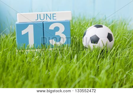 June 13th. Image of june 13 wooden color calendar on green grass background with football outfit. Summer day.