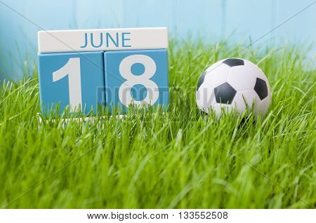 June 18th. Image of june 18 wooden color calendar on green grass background with football outfit. Summer day.