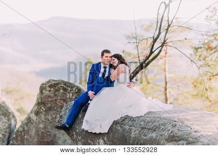Romantic newlywed couple sitting on boulder's edge, bride's long dress spreading rock. Hills landscape as backround.