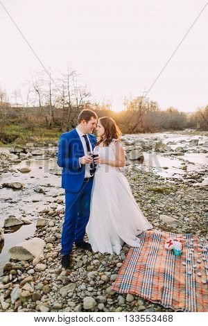 Romantic young newlywed couple drinking wine on rocky pebble river bank with forest hills and stream as background.