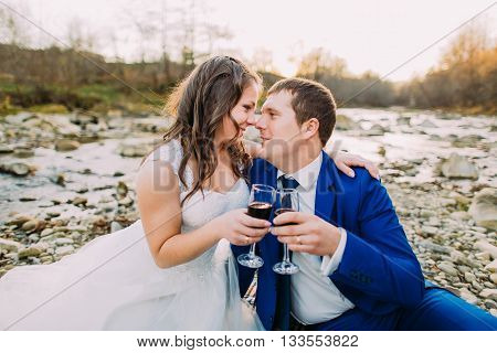 Romantic young bridal pair drinking wine on rocky pebble river bank with forest hills and stream as background.