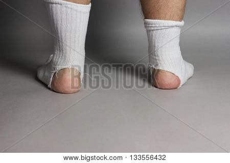 back of standing feet with white socks and a big hole in front of grey background