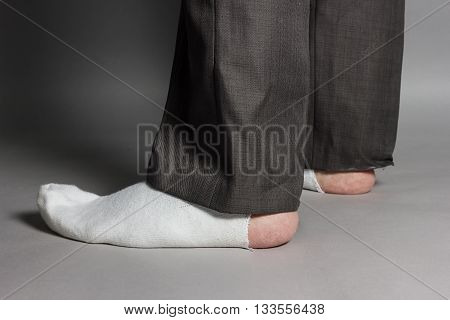 sideways standing feet with white socks and a big hole in front of grey background