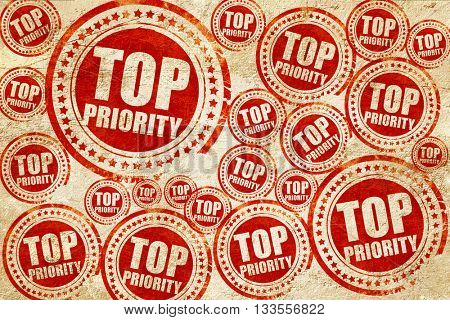 top priority, red stamp on a grunge paper texture