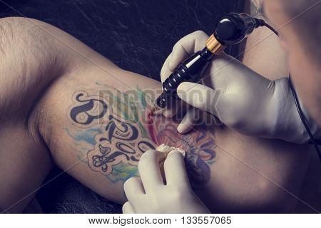 Male tattoo artist showing the process of making a tattoo on arm. Colorful tattoo art on human body and skin. Tattooist holding an active machine or gun.