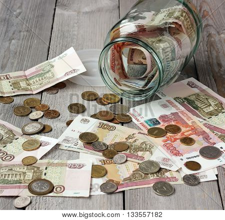 Glass jar and Russian money (paper and coin) on the wooden floor. The concept of storing money deposits. Rubles and kopeks a small amount of money.