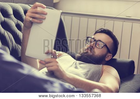 Male model lying on a couch in a living room surfing the web on a tablet computer