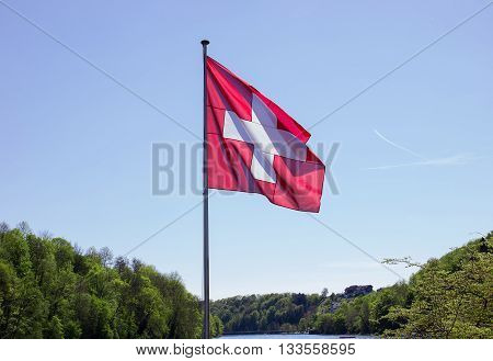 waving swiss flag over river and forest