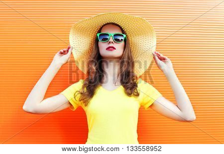 Fashion Pretty Woman In Sunglasses And Straw Hat Over Colorful Orange Background