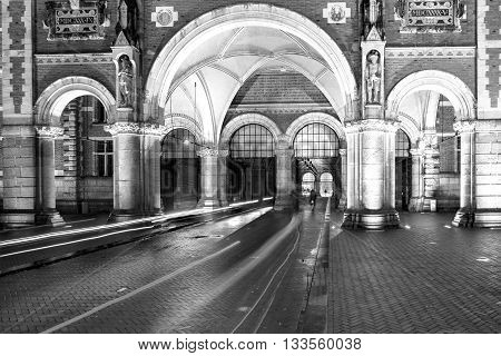 Cyclists ride through Rijksmuseum arch at night. Amsterdam Netherlands Europe