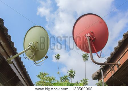Orange green Satellite Dishes under blue sky Mounted on the back of the house.