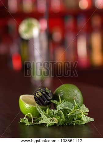 Muddler mint leaves and limes on a bar counter