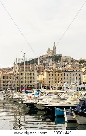 Old seaport city of Marseille. Yachts sailboats houses and views of the Notre-Dame de la Garde.