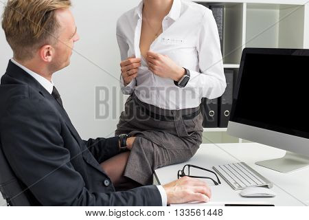 Secretary opening her blouse in front of her boss