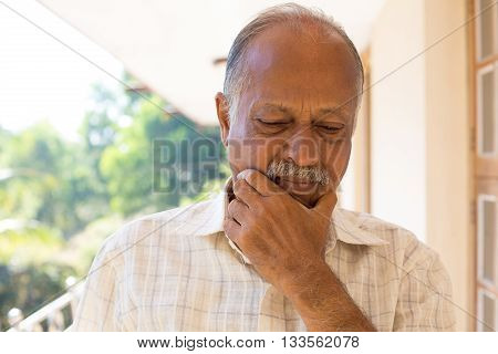 Closeup portrait morose elderly pensioner downcast gloomy isolated outside outdoors home background