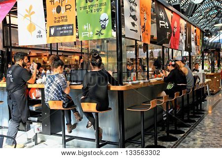 TEL AVIV, ISRAEL - APRIL 7, 2016: People having lunch in a modern open kitchen restaurant in the new Sarona food market, Tel Aviv, Israel
