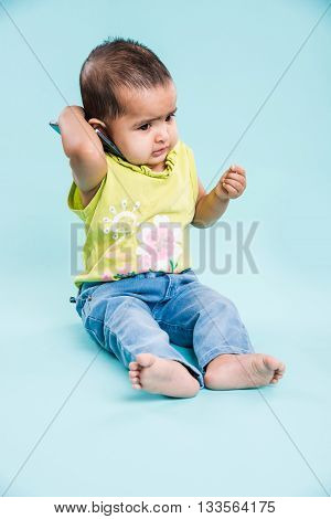 Happy baby girl talking on mobile phone isolated on blue. Closeup. Indian little girl and mobile or handset, asian baby girl using smartphone