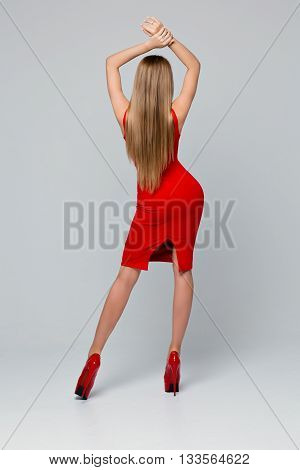 Beautiful slender woman standing backwards. Rear view of a beautiful red dress, red shoes with high heels. Fashion, beauty. Inside, Studio background