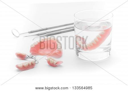 Set of Denture in glass of water and tools on white background