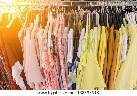 Choice of fashion clothes of different colors on metal hangers in a weekly cloth market - Shopping addiction concept - Main focus in a middle of the frame