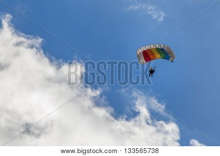 Parachuting skydiver descends by parachute through the clouds