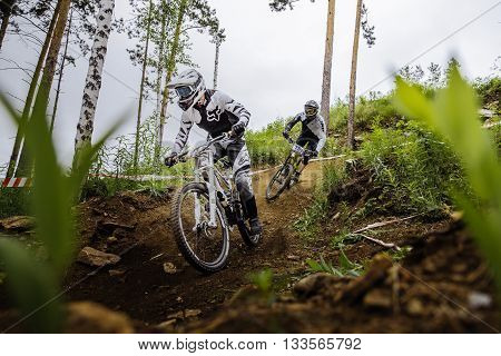 Miass Russia - May 29 2016: two riders of athlete on bike down through woods from mountain during Cup